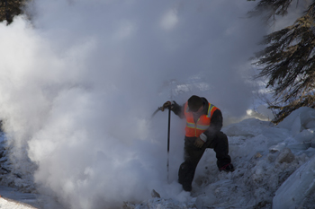 a road worker stands in a cloud of steam