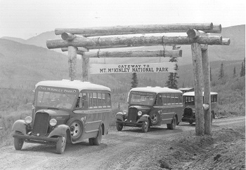 historic photo of buses driving under a wooden archway that read Mt. McKinley National Park