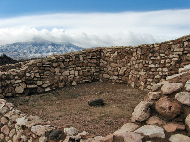 Walls of a room in Tuzigoot Pueblo, with a view of cloud-shrouded mountains in the distance