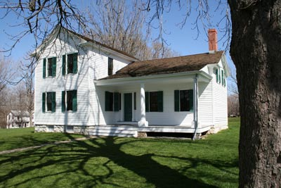 A two story house with white siding, green shutters, and a porch on one side, surrounding by lawn.