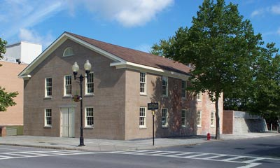 A rectangular, sand-colored two-story building sits on the corner of two streets.