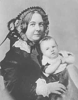 A women in a lace-collared dress and hat holds a baby to face the photographer.