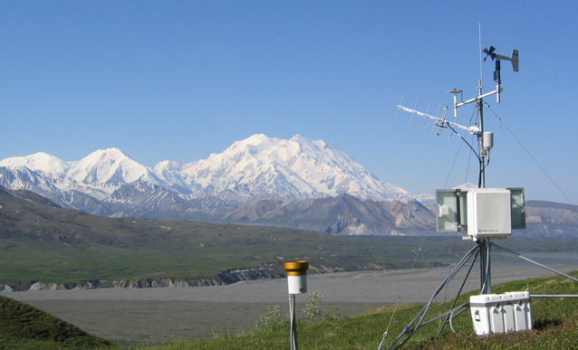 a weather station stands on a hillside with Denali in the background