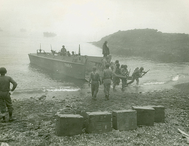 Uniformed soldiers carry gear off a boat onto a rocky beach.