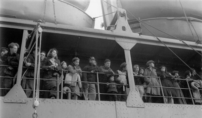 A crowd stands at the railing of a ship, looking off into the distance.