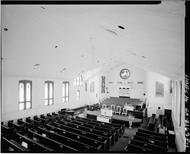A high angle view of the pulpit, organ, and pews within the white-walled interior of a church.