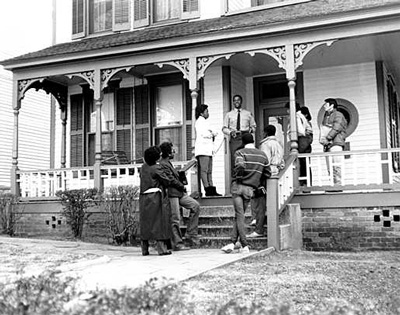 A tour guide stands on the porch of a house and speaks to a gathered group.