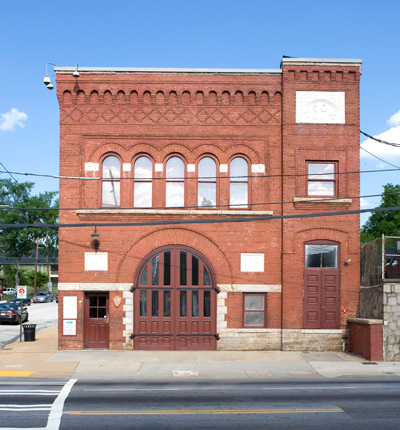 The fire station is a rectangular, red brick building with arched doors, windows, and brickwork.