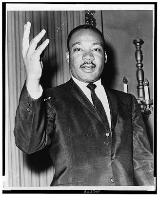 Half-length portrait of Dr. Martin Luther King, Jr., facing front with right arm lifted.