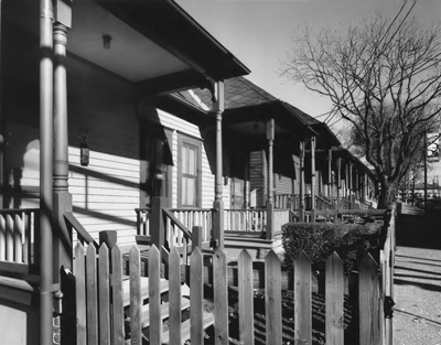 Wooden fencing surrounds the small yards and porches in front of a row of shotgun homes.