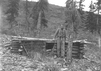 Adolph sits on the remnants of a trapper's cabin