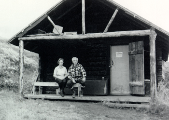 Adolph and his wife sit in front on a log cabin