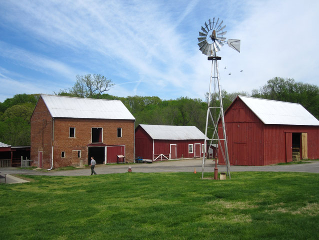 Wispy clouds above a windmill, farm buildings, and a bright green lawn.