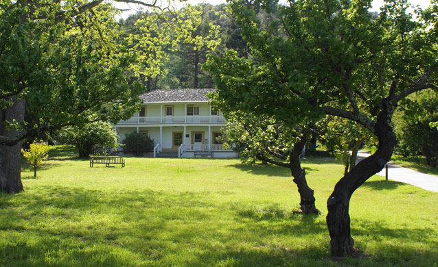 A two-story white house with a porch along both levels stands beyond orchards and lawn.