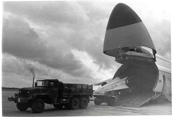 An army truck unloads a missile from an air carrier.