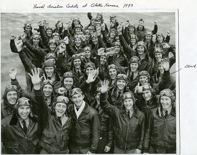 A large group of smiling men in aviator jackets, hats, and goggles raise their hands for the camera.