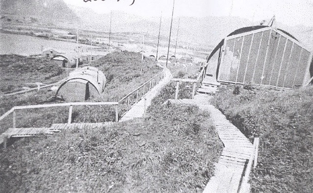 Board walks and Quonset huts in a grassy area