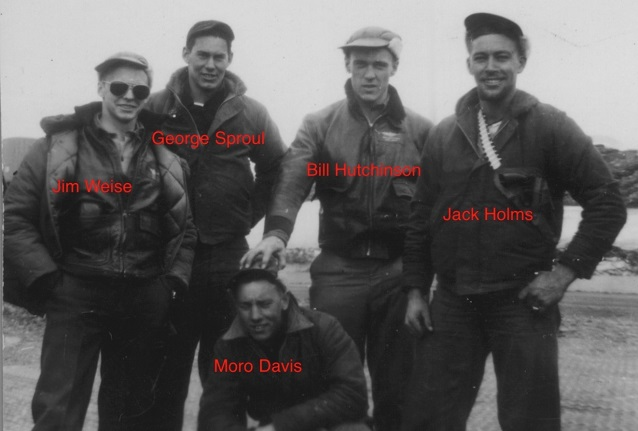 Five men in military wear pose for a photo