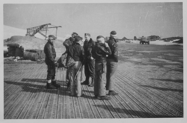 A group of men in bomber jackets stands on an airplane runway