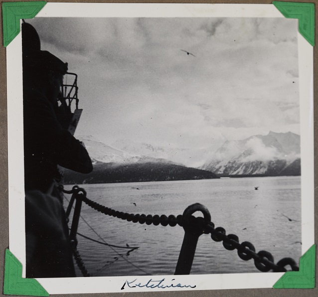 Black and white image of mountains across the water from behind a chain.