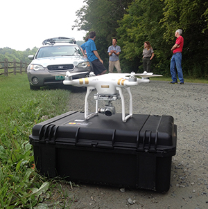 Close-up view of a quadcopter unmanned aircraft and three people.