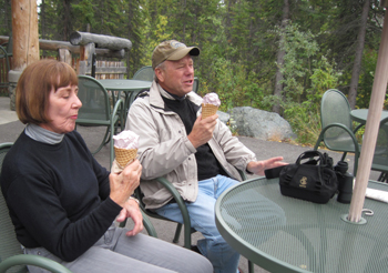 Two adults enjoy an ice cream cone.