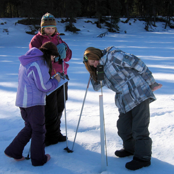 Students use a snow probe to measure snow depth and temperature.