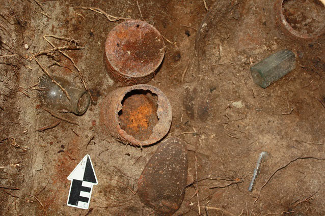 Rusted cans, glass bottles, and shoe soles in dirt with an arrow marking north