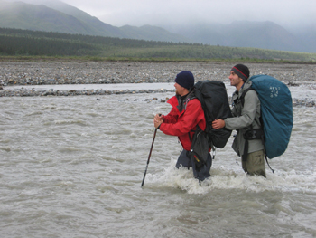 Two backpackers crossing a glacial river.