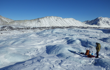 a researcher stands on a glacier