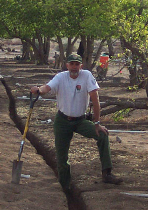 A man in NPS uniform poses with a shovel in an orchard.