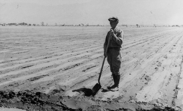 A man stands in the tip of his shovel resting in an irrigation ditch in a flat, open field.