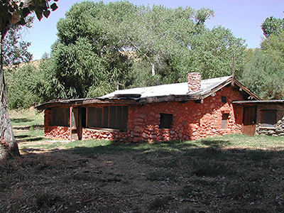A single-story house of rough stone construction stands in the shade of leafy cottonwood trees.