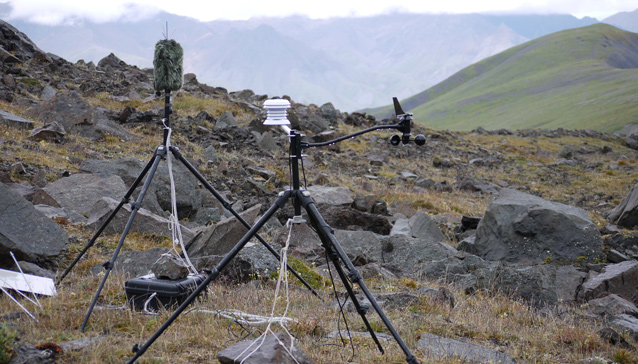 two tripods hold sound recording equipment sit on a rocky hillside