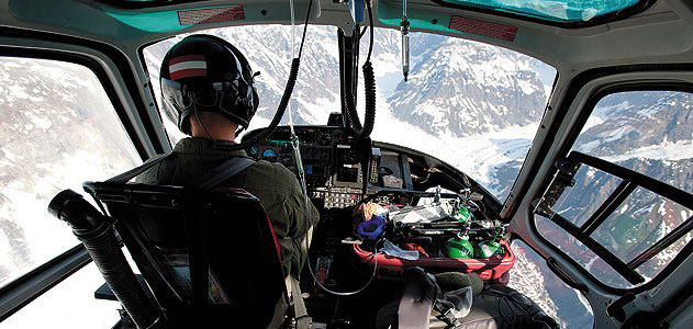 view of pilot from inside a helicopter flying over snowy mountains