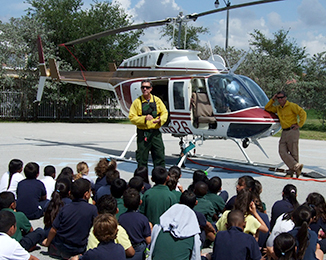 group of students sitting in front of a helicopter listening to the pilot