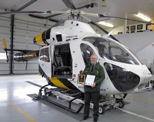 Man standing in front of a helicopter
