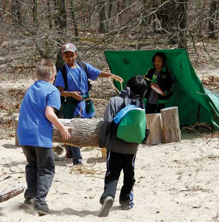 Children create a shelter using tarps and logs at Nature Play Zone