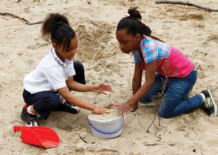 Two Gary, Indiana, students dig in the sand at the Nature Play Zone