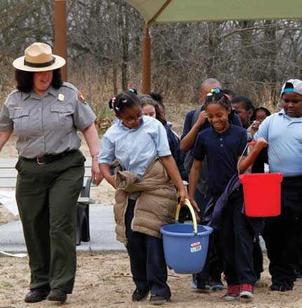 A park ranger leads a group pf schoolchildren in the Nature Play Zone