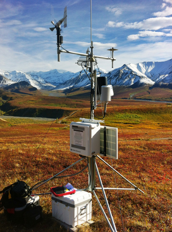 a climate station stands amidst fall-colored tundra
