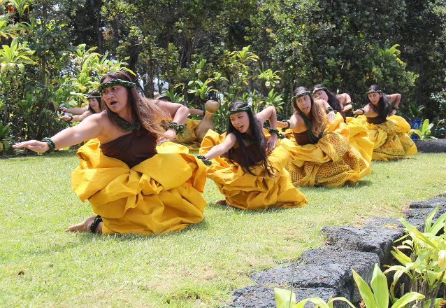Women in traditional Hawai'ian dress crouch in a line to demonstrate a hula dance step