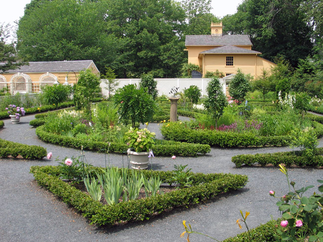 Geometric plantings in the formal garden are punctuated by planters, trees, and boxwood edging.
