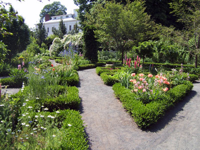 A gravel path leads around beds of colorful flowers, framed by boxwood hedges.