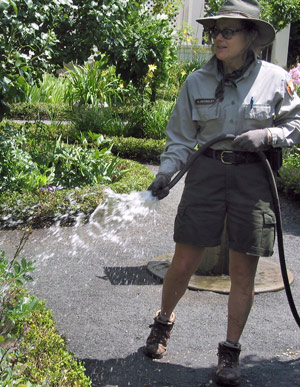 A woman in NPS uniform, in shorts and a hat, sprays water from a hose onto the edge of a garden.