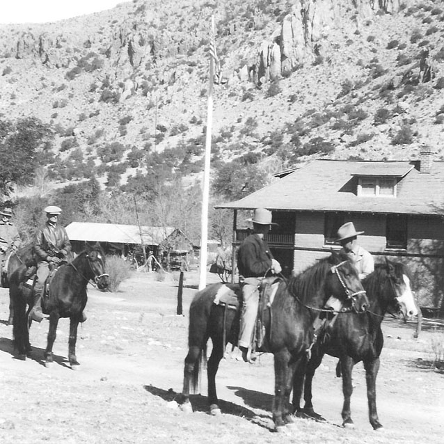 Three people on horses in front of Faraway Ranch buildings