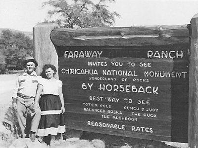 Two visitors pose by a sign for Faraway Ranch advertising trips by horseback to Chiricahua NM