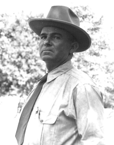 Portrait of Ed Riggs in a shirt and tie, and a brimmed hat