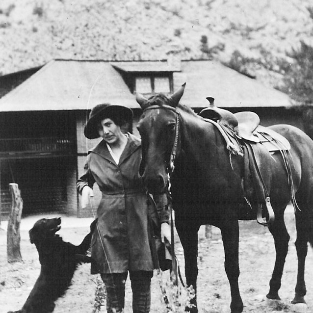 Lillian Erickson Riggs stands between a dog and a horse at Faraway Ranch