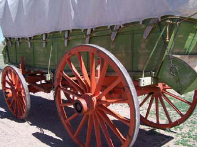 Side view of a green-colored covered wagon with red wheels.